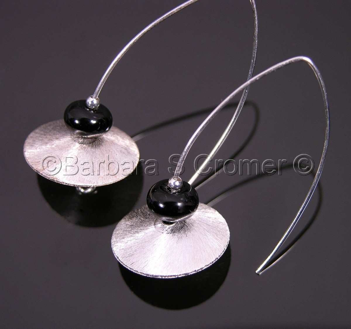 brushed Sterling silver saucers, topped with black Venetian lamp work, and suspended on handmade, Sterling silver arc wires, to create simple, elegant earrings. (large view)