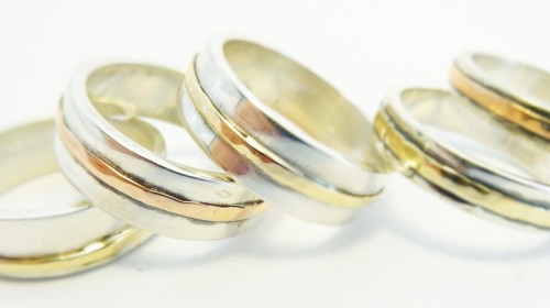 Sterling silver wedding ring encircled with gold.