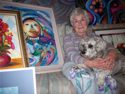 25 Doree at home with her dog, Shayna, and some of her paintings.