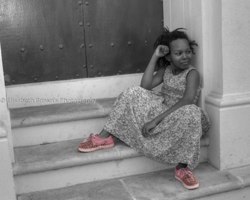 Little girl sitting on a step.