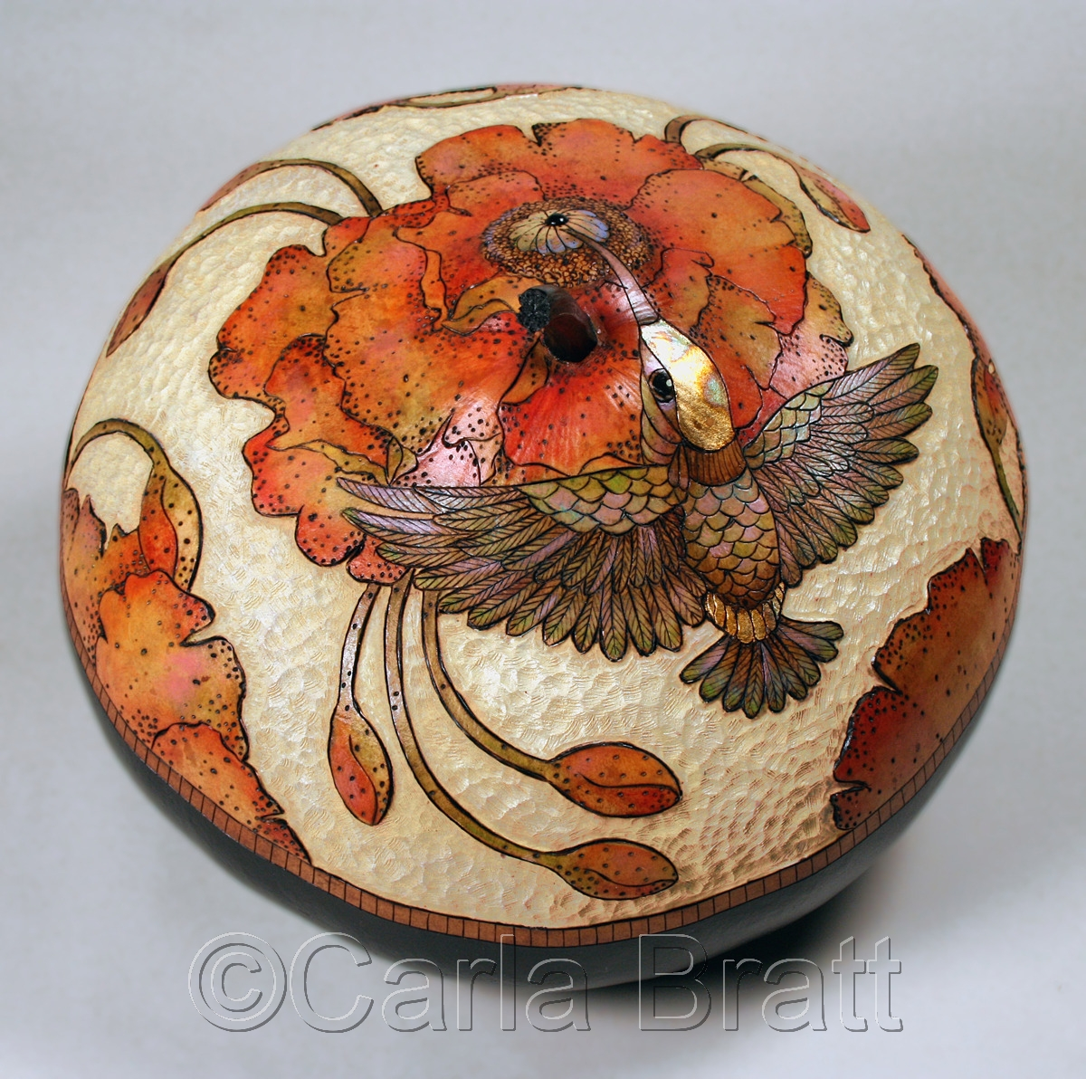 Medium sized fine art  canteen gourd with hummingbird & poppy image, wood burned & hand painted against a carved ivory background. Reds, oranges, browns, blues, purples & greens are the predominate colors. By gourd artist & printmaker, Carla Bratt. (large view)