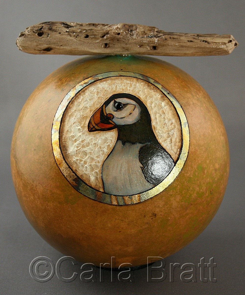 Medium round gourd with Puffin bird image, against a carved background with metal leaf accent. Hand painted & weighted with beach sand , with a found drift wood topper. By gourd artist & printmaker, Carla Bratt (large view)