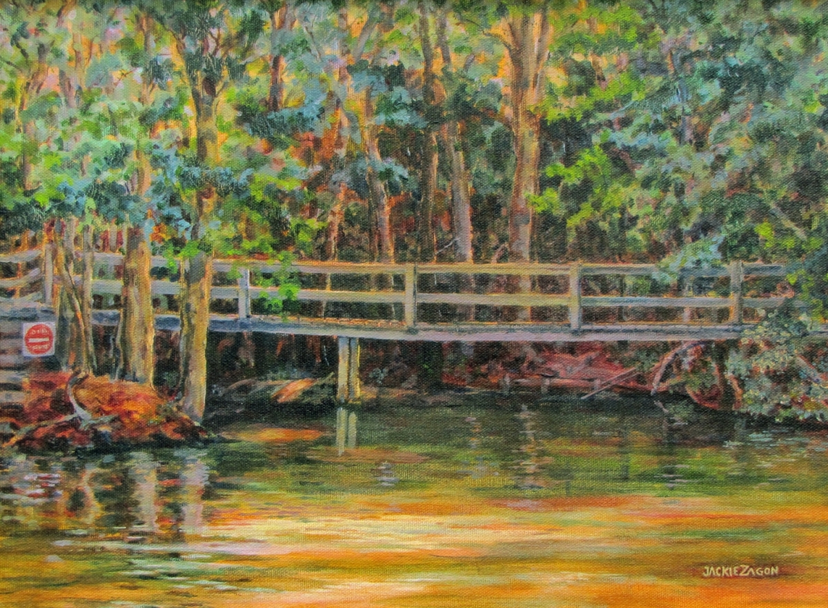 "Jackie Zagon, Acrylic on canvas mounted on  board. Landscape. A crumbling, wooden bridge spans a narrow river in the woods while a late summer sun is setting. A ""No Entry"" sign prohibits traffic. The transitions represent the time of day, the seasons & th (large view)"
