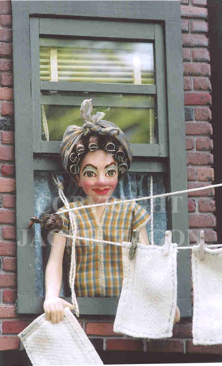 Jackie Zagon, Wall sculpture series, Mixed media. A New York City 1950's tenement building window with a lady in curlers & headscarf & housedress while hanging her laundry. Great miniature detail in high relief, using both new & recycled materials.  More (large view)