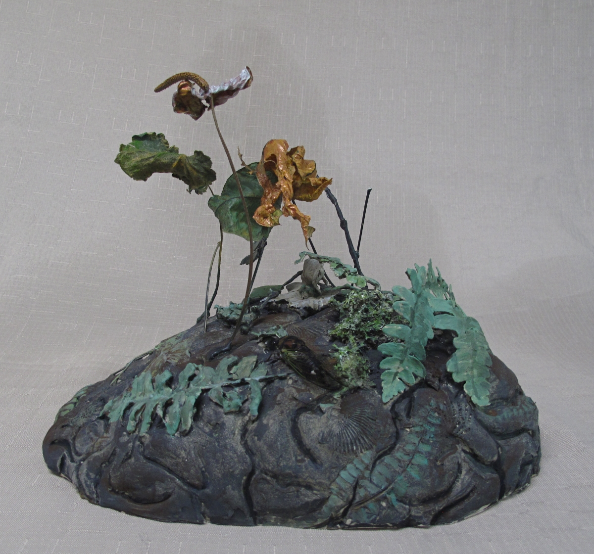 """A ceramic brain is the ground for a botanical landscape sprouting actual dried and ceramic plant forms and a cicada bug.  13""""h. X 15""""l. X 12""""w. in custom plexi display cube. (large view)"""