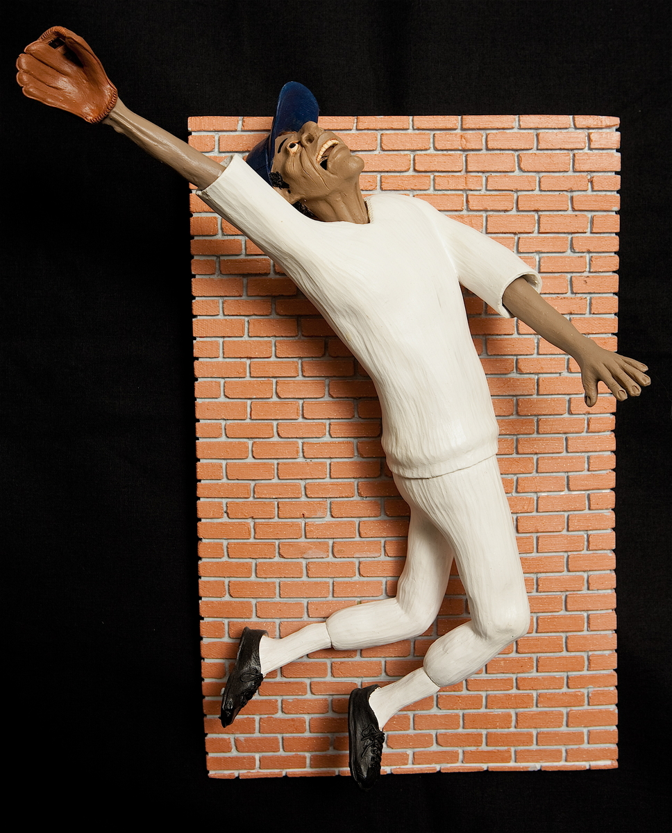 This is a three-dimensional baseball player against a bas relief brick wall.  The stop action catches him in midair as he attempts to catch the ball.  He wears a generic white uniform. (large view)