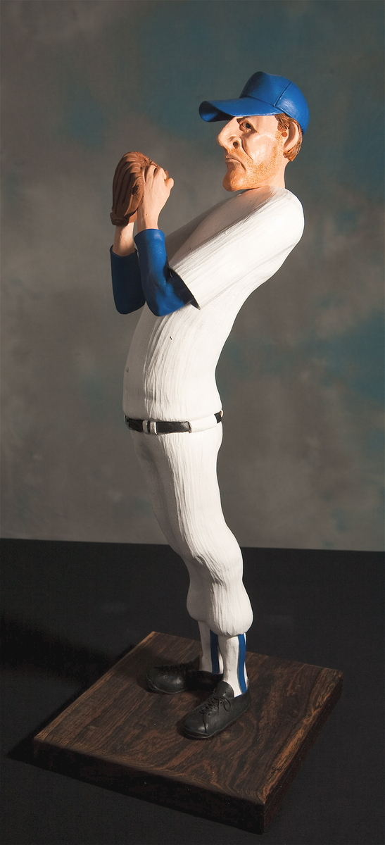 The baseball pitcher is a hand-built ceramic sculpture mounted on a hardwood base.  Great detail on the mitt, shoelaces, and beard stubble.  Generic white uniform with blue shirt and hat. (large view)