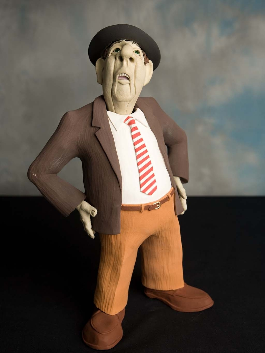 This clay figure wears a hat, brown jacket, and striped tie.  He's gazing upward with hands on hips. (large view)
