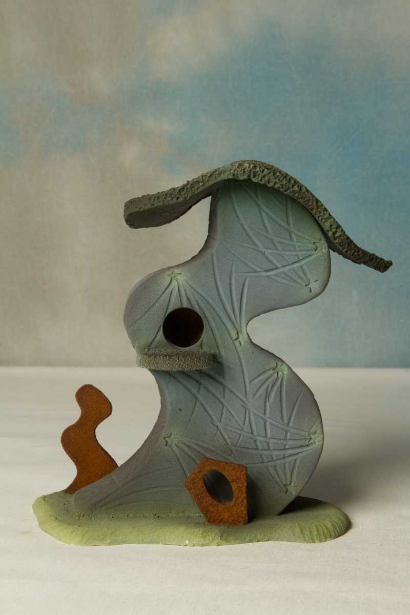 This small, imaginative dwelling is a slab built sculpture, created with stoneware clay.  The bright underglaze colors on the highly textured surfaces emphasize the uniqueness of this  (large view)