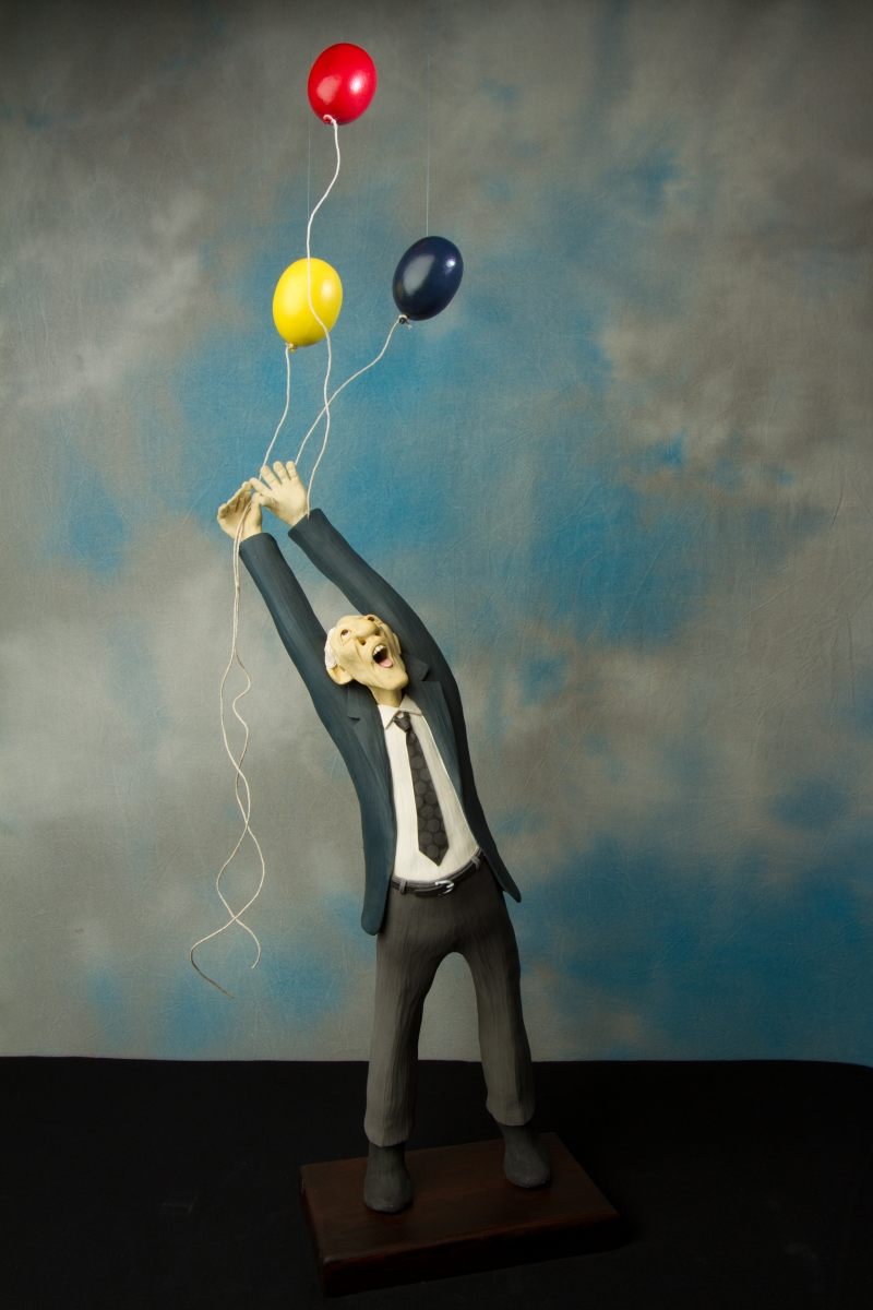 Clay figure of a man reaching up, distressed at losing a bunch of balloons.  The brightly colored balloons' strings gracefully curl with the wind as they float up and out of his hands. (large view)