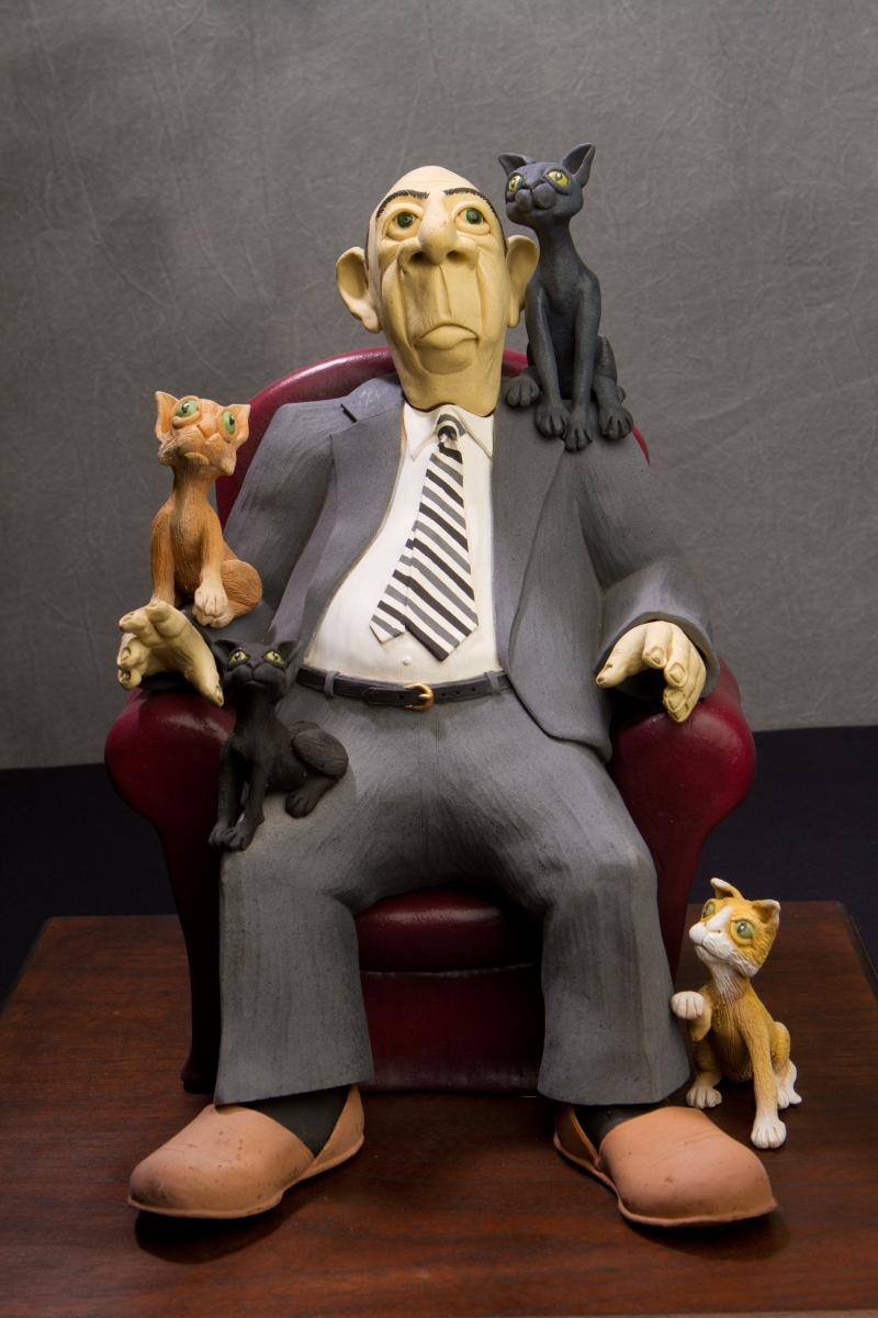 A hand-sculpted clay figure shown seated in a big dark red chair.  Four cats placed on and around him are there to show the importance of the therapeutic presence of precious pets. (large view)