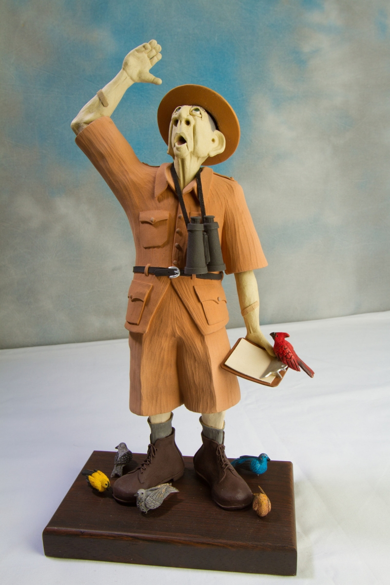 This is a hand built clay figure of a birdwatcher, dressed in his outdoor hiking attire, with binoculars and  clipboard.  He appears to have spied another bird up above him while at his feet are several other birds and one on his clipboard. (large view)