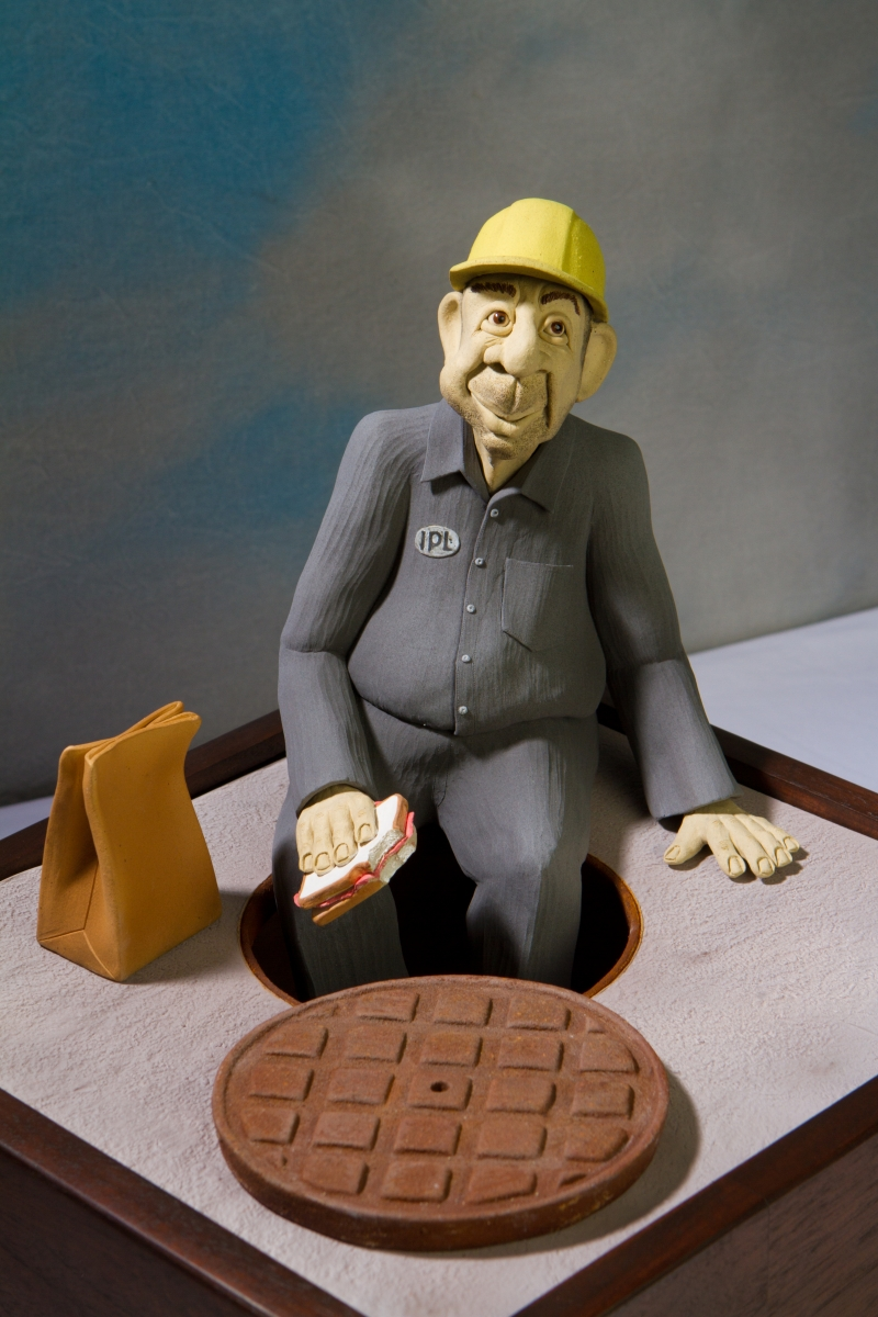 This is a hand built clay figure of a utility worker seated on the street with legs dangling down the manhole.  A rusty cover lays nearby, his lunch sack next to him,  he's eating his sandwich. He wears work clothes and hard hat. (large view)