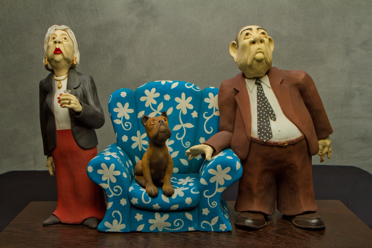 This is a hand built clay sculpture of a married couple and their pet dog.  Posing for a family portrait, it's evident that pets and their owners often resemble each other.  The gaudy chair emphasizes their appearance. (large view)