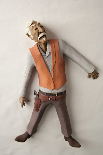 This ceramic cowboy sculpture lies flat on his back.  He's wearing brown boots and pants, a vest, and holster with gun. (large view)