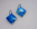 Square titanium earrings, hung from titanium wires at a diagonal. Heat, by means of a small torch is used to produce this vivid, iridescent blue color with white accents. Available in 3 sizes (thumbnail)