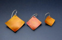 Lightweight, orange aluminum square earrings are positioned at a diagonal and hung from sterling silver wires. Available in 3 sizes. (thumbnail)