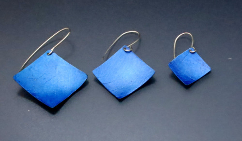 Lightweight, blue aluminum square earrings are positioned at a diagonal and hung from sterling silver wires. Available in 3 sizes. (thumbnail)