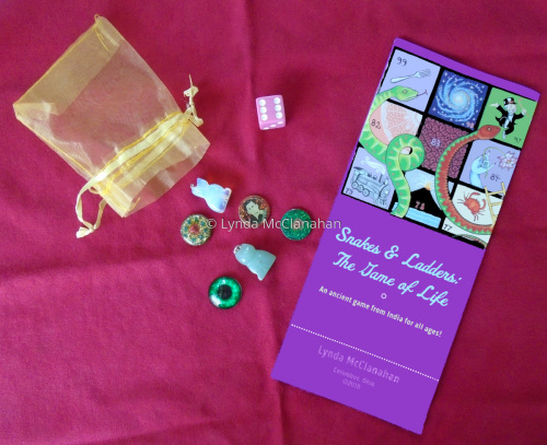 "Brochure and game pieces for ""Snakes & Ladders: the Game of Life"""