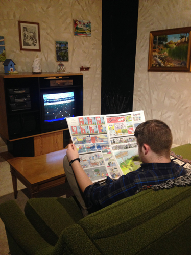 Seated viewer reading Sunday Comics Section
