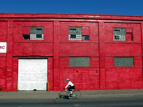 Bike Rider Against Red Building by LOCAL COLOR EDITIONS  .  FEATURING THE ART AND DESIGN OF MICHAEL MORGULIS