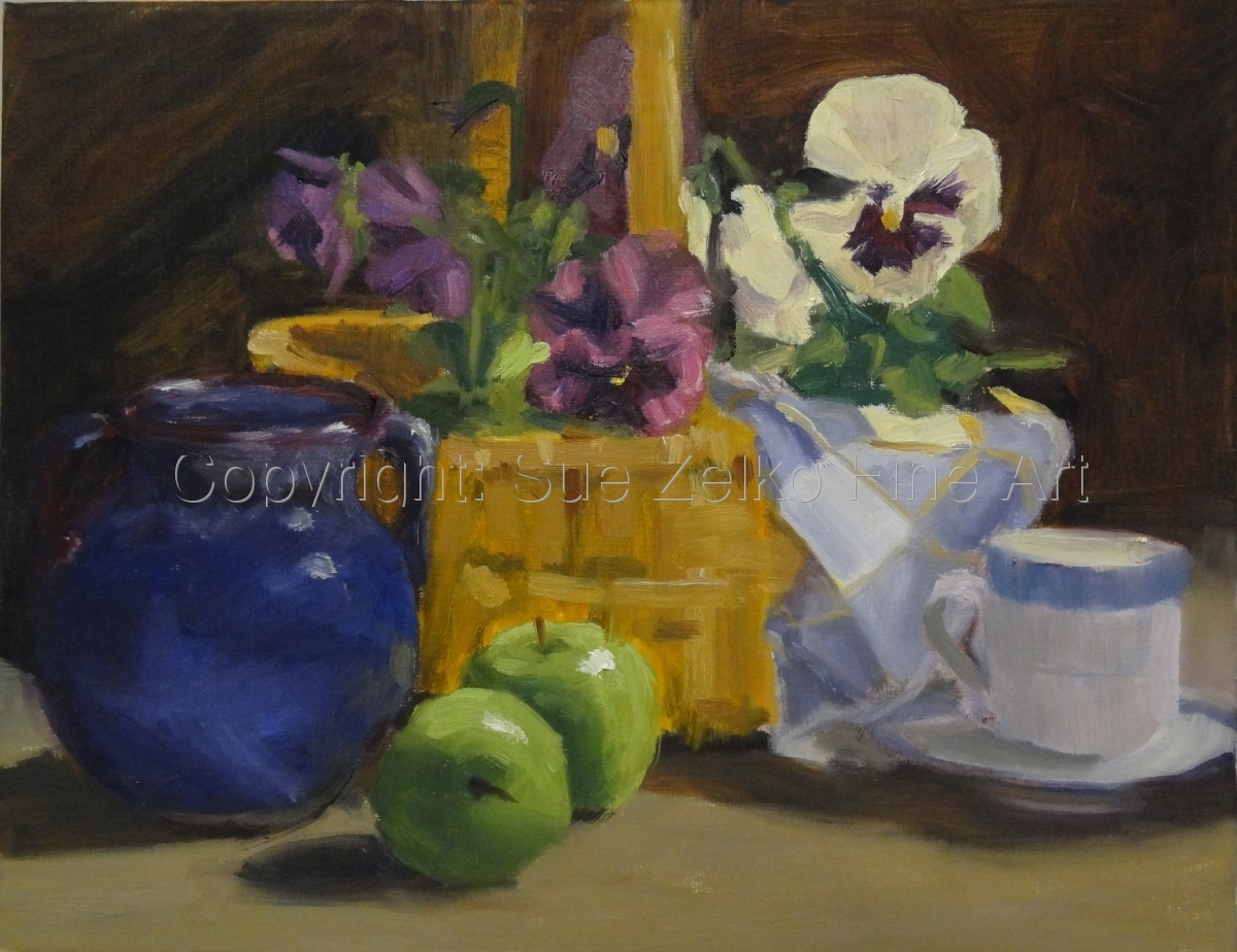 Still life painting of a basket of pansies arranged with a blue jug, cup and saucer and 2 green apples (large view)