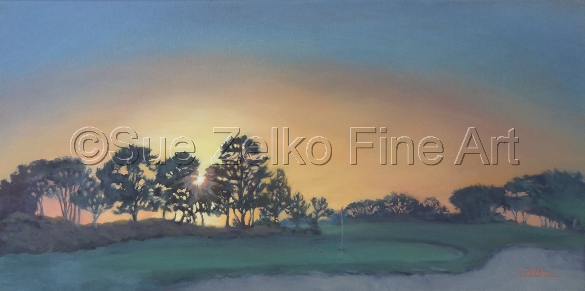 Silhouetted pine trees against a brilliant sunset behind a golf green in shadow (large view)