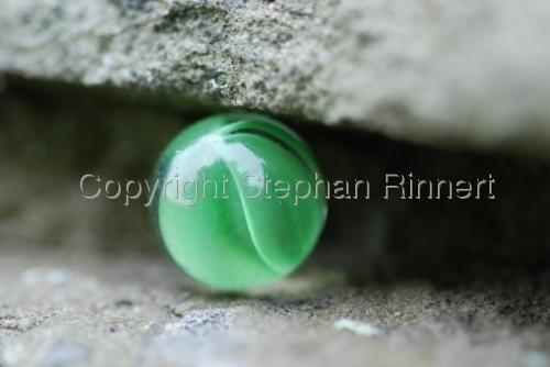 Green Marble Caught Between Rocks