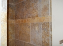 View of hand-made tumbled marble border in guest bathroom shower. (thumbnail)