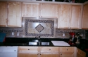 Kitchen backsplash make from small black stones and porcelain tiles Carrillon Parkway. (thumbnail)