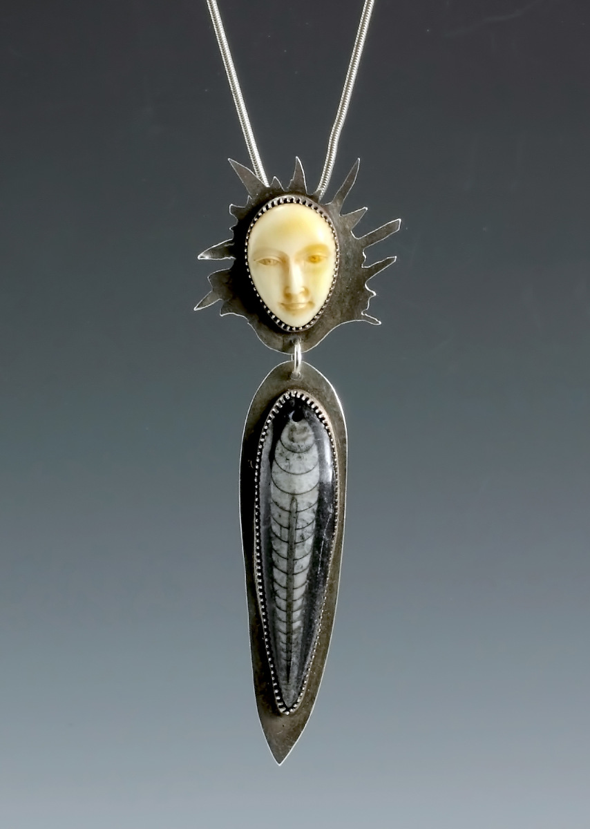 Unique piece with handcarved bone face and fossil body set in sterling silver (large view)